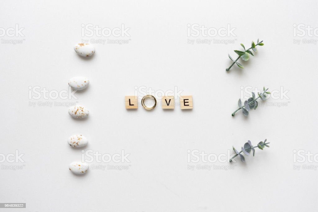 Wooden letters and wedding rings spelling love, with candies and oregano branches. Top view. royalty-free stock photo