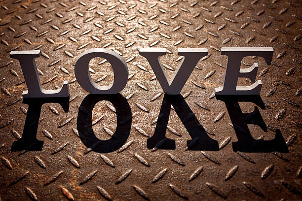 Wooden letters forming word LOVE written on metallic background stock photo