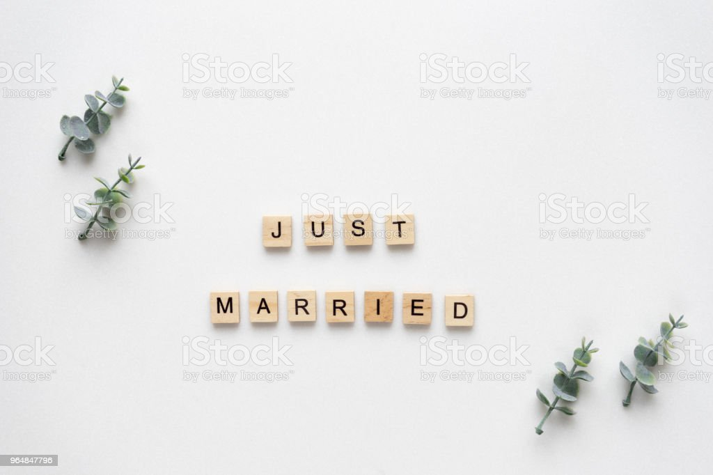 Wooden letters  speling just married with oregano branches on white marble. Top view. royalty-free stock photo