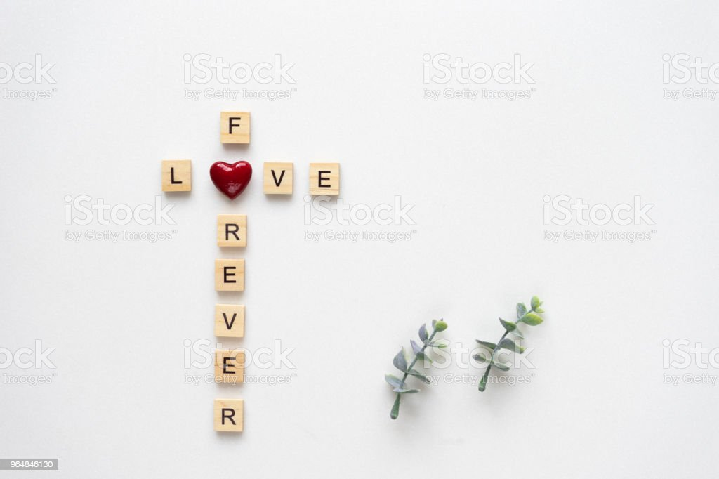 Wooden letters  speling love for ever, with oregano branches on white marble. Top view. royalty-free stock photo
