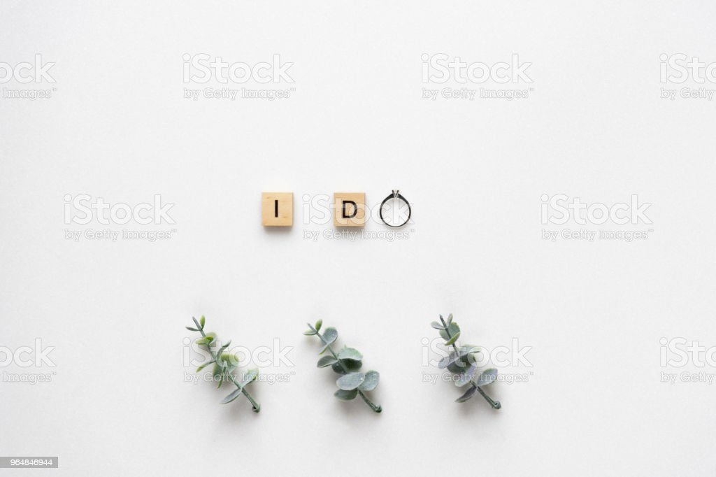 Wooden Letters Spelling I Do With Engagement Ring Oregano Branches On White Marble Top View Stock Photo & More Pictures of Candy