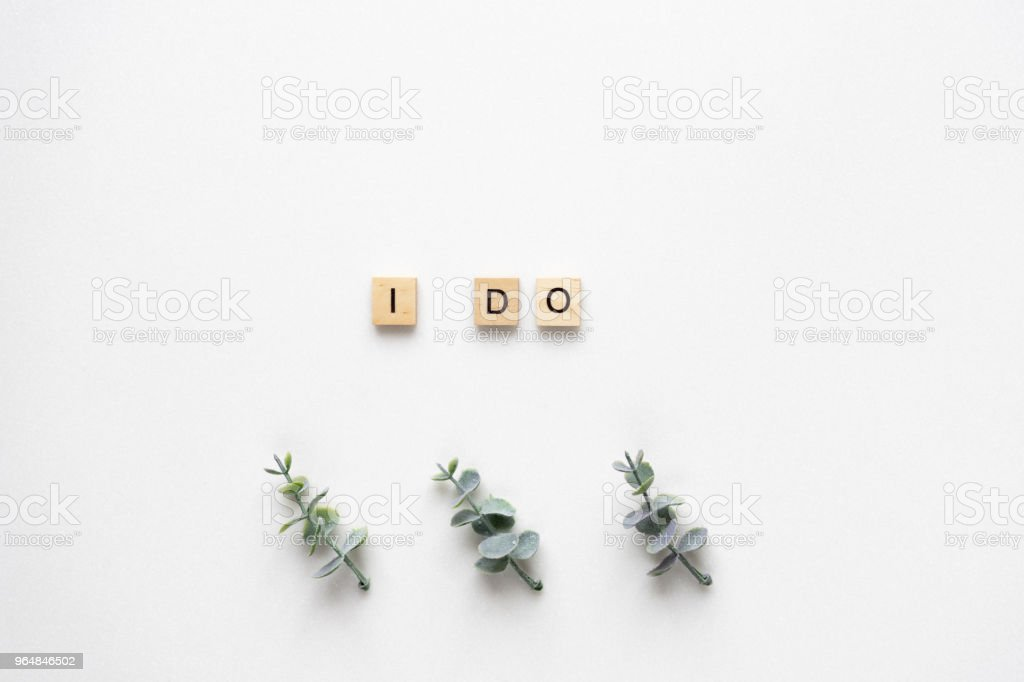 Wooden letters  spelling I do with oregano branches on white marble. Top view. royalty-free stock photo