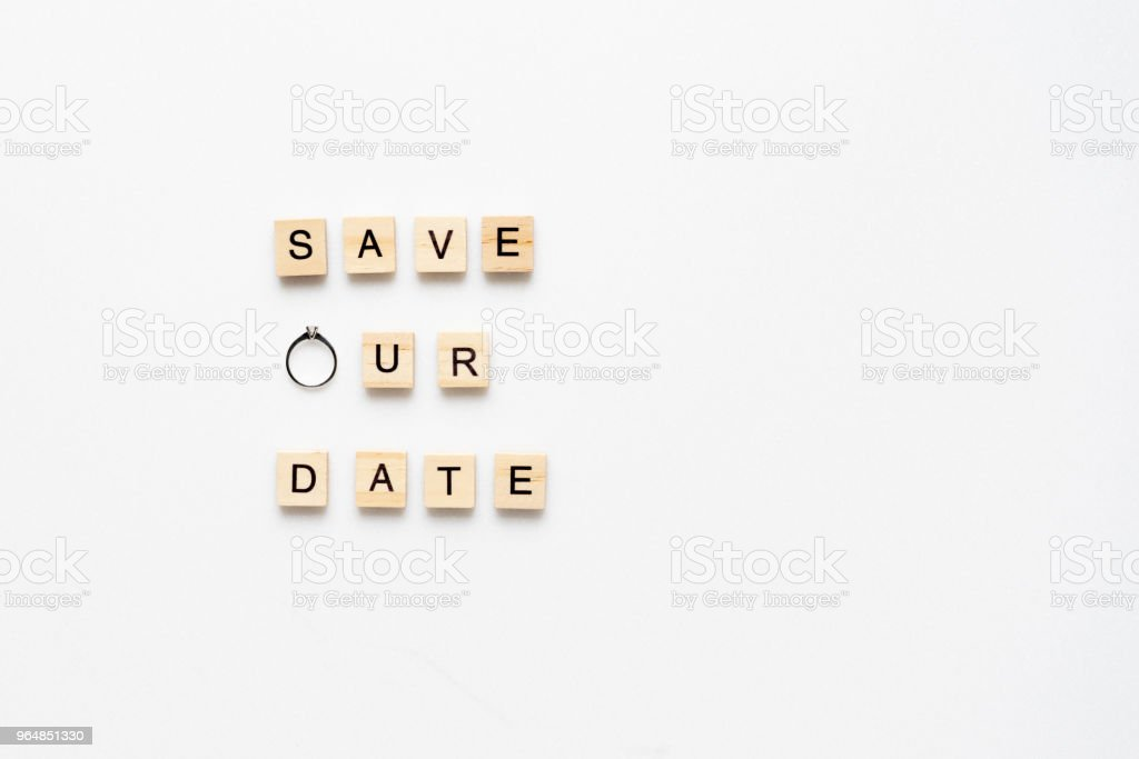 Wooden letters  spelling save our date and engagement  ring on white marble. Top view. royalty-free stock photo
