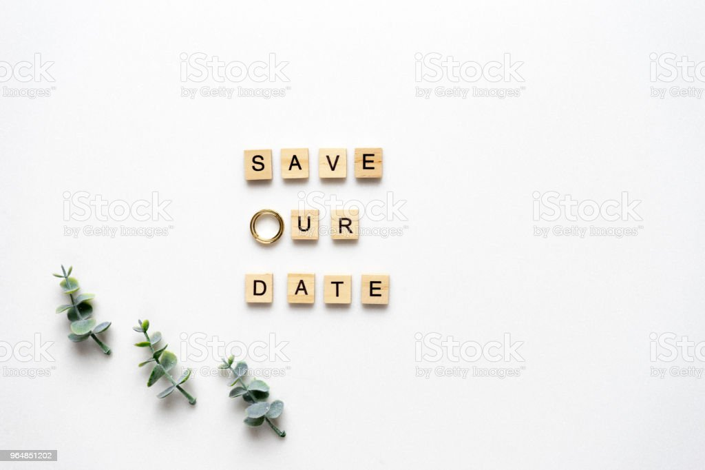 Wooden letters  spelling save our date, oregano branches and wedding rings on white marble. Top view. royalty-free stock photo