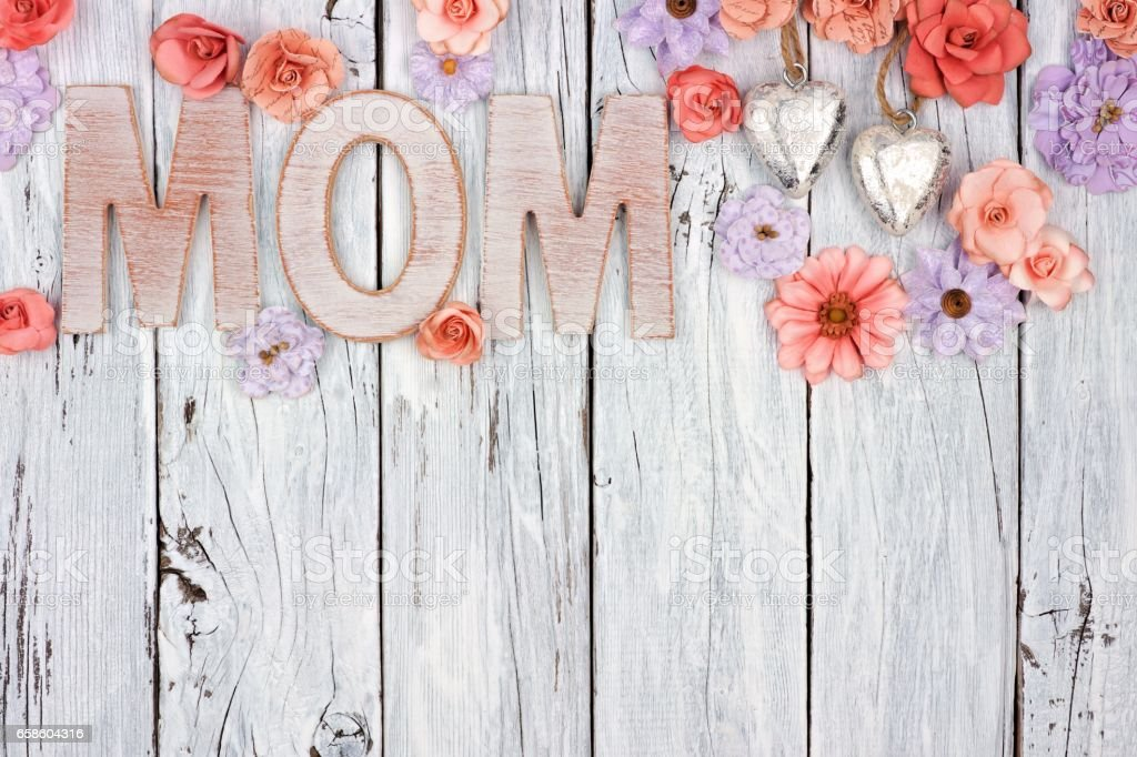 mom wooden letters with top border of flowers against white wood royalty free stock photo