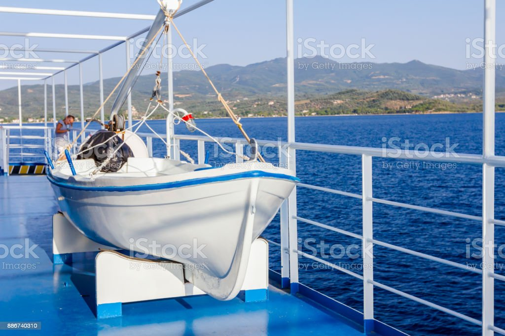 Wooden lifeboat on davits mechanism, rowboat stock photo