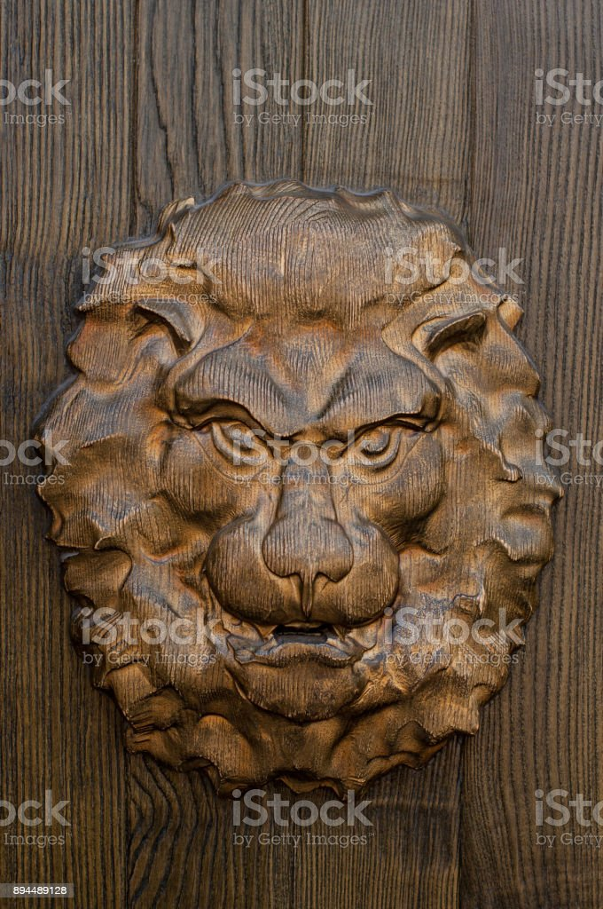 Wooden lion head on the gate stock photo