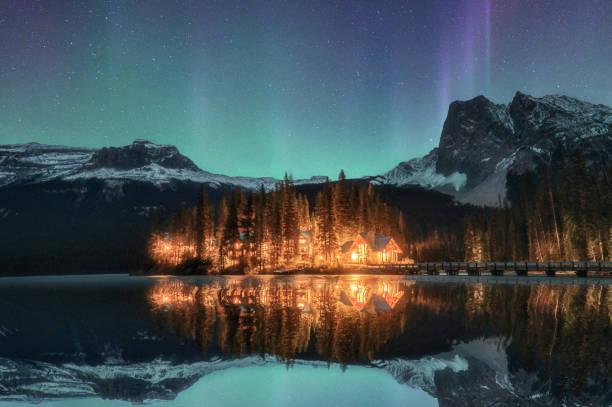 Wooden lodge illuminated with Aurora borealis on Emerald lake at Yoho national park stock photo