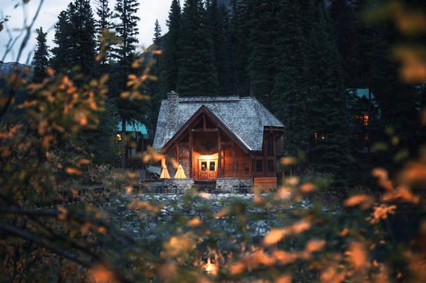 Wooden lodge illumination with autumn leaves on Emerald Lake at Yoho national park stock photo