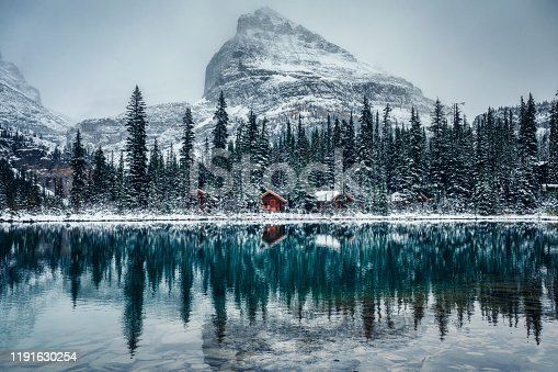istock Wooden lodge in pine forest with heavy snow reflection on Lake O'hara at Yoho national park 1191630254