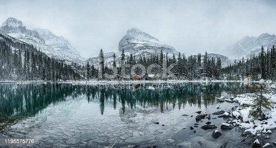 Panorama of Wooden lodge in pine forest with heavy snow reflection on Lake O'hara at Yoho national park, Canada