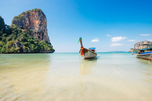 Wooden Longtail Boat in Tropical Railay Beach in Krabi Thailand stock photo