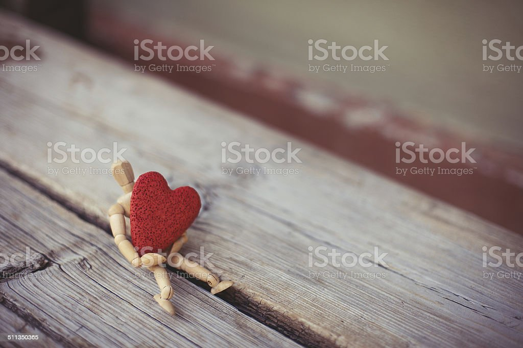 wooden man and a big red heart stock photo