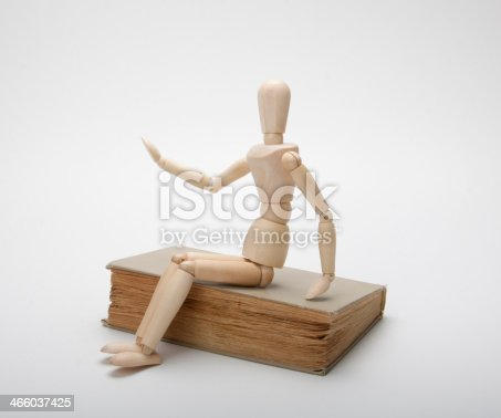 153178960istockphoto Wooden man and book 466037425