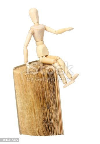 153178960istockphoto Wooden man and book 466037427