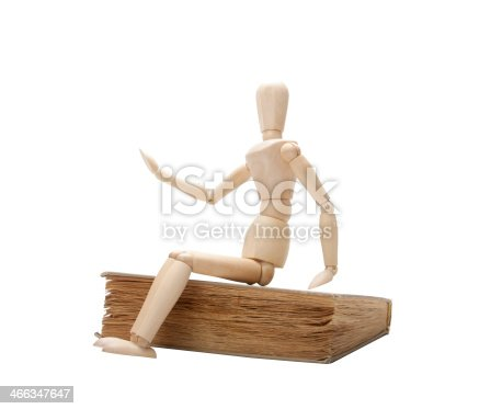 153178960istockphoto Wooden man and book 466347647