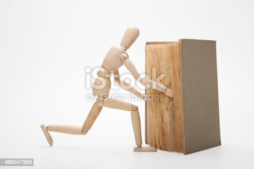 153178960istockphoto Wooden man and book 466347935
