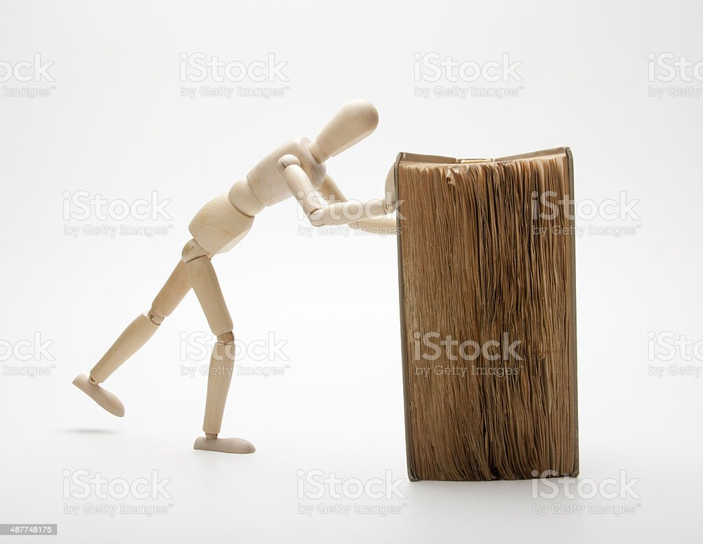 Wooden man and book stock photo