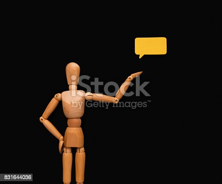 istock Wooden man with speech bubble, black background 831644036