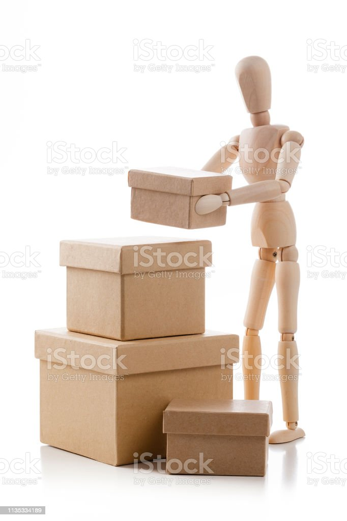 Three quarters front rear of a wooden mannequin arranging a stack of...