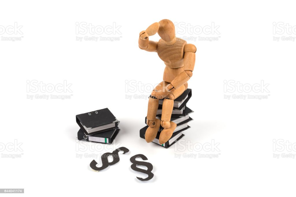 wooden mannequin as the thinker of rodin on folders and law stock photo