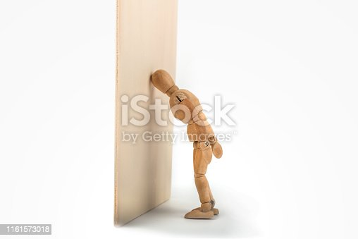 Wooden mannequin bangs his head against the wall - face palm