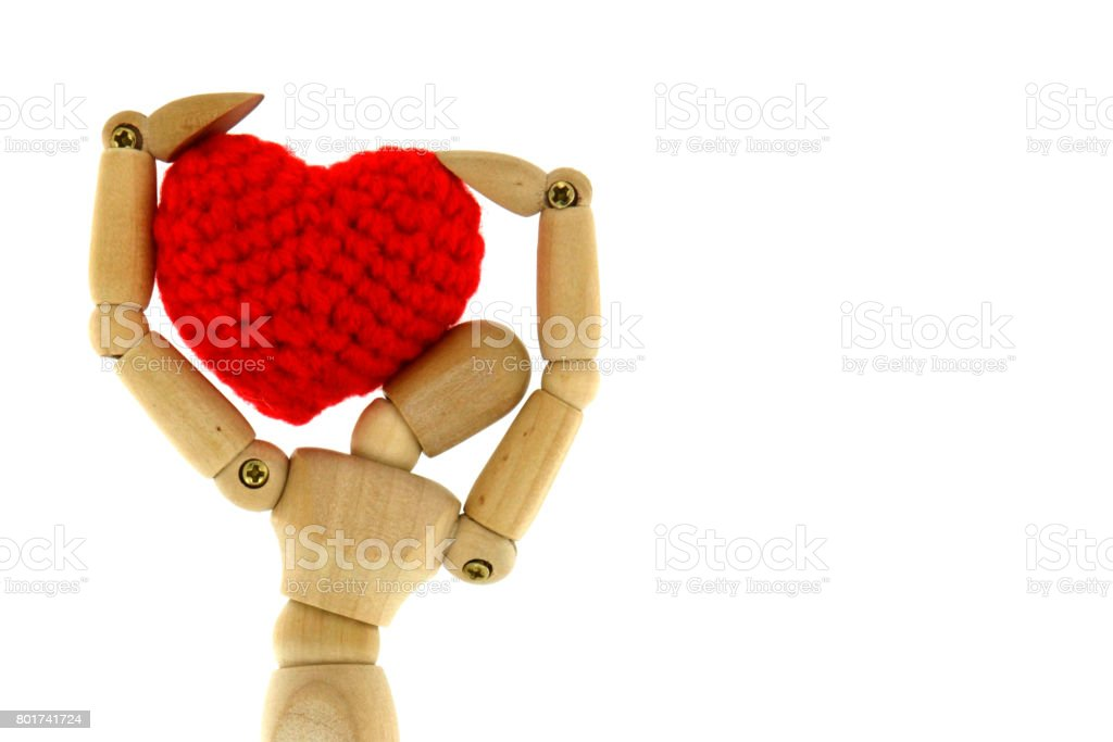 Wooden mannequin carry heart knit with yarn stock photo