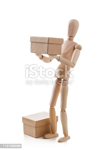 Three quarters front view of a wooden mannequin standing on white background carrying or delivering a cardboard box. A second cardboard box is beside the mannequin placed directly on the floor. Predominant colors are brown and white. High key DSRL studio photo taken with Canon EOS 5D Mk II and Canon EF 100mm f/2.8L Macro IS USM.