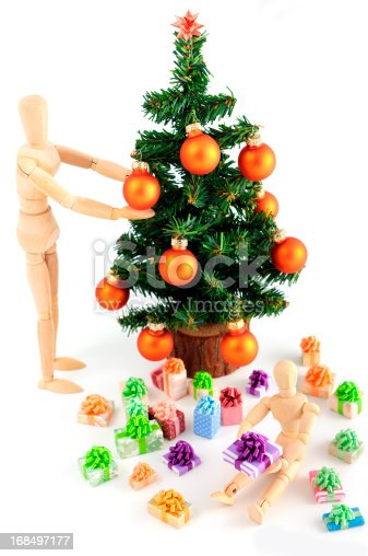 istock wooden mannequin decorating christmas tree and gifts 168497177