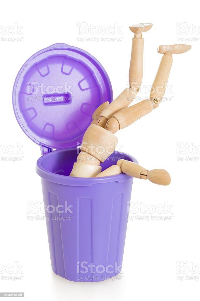 Wooden mannequin doll upside down in purple dustbin stock photo