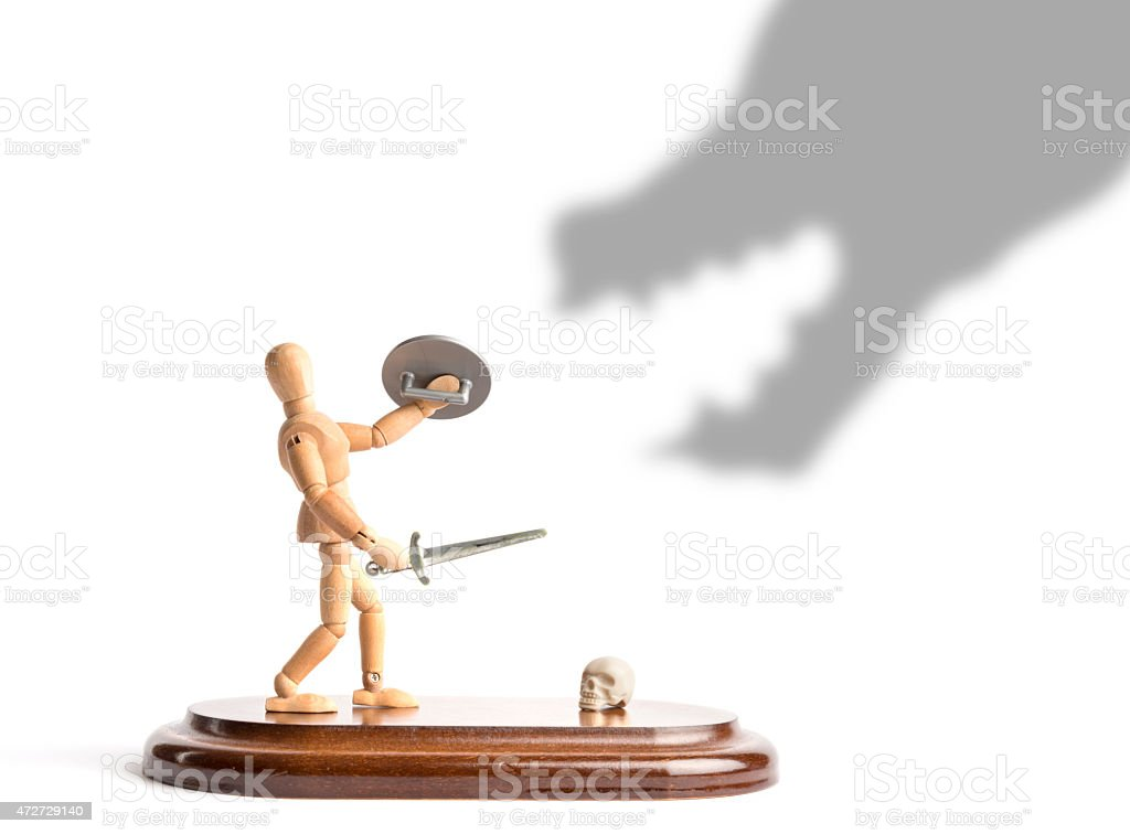 wooden mannequin fighting with sword against dragon shadow stock photo