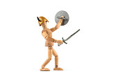 Wooden mannequin fights with sword and shield against an enemy