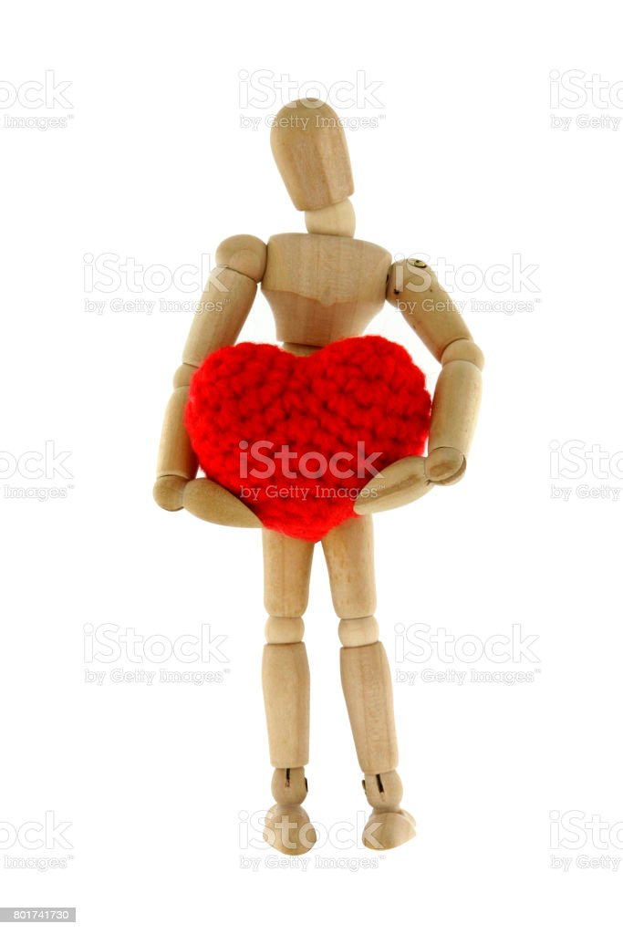 Wooden mannequin hugging heart knit with yarn stock photo