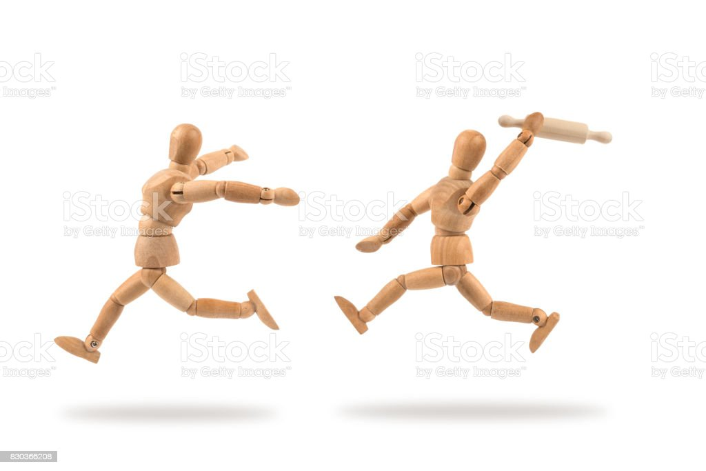 Wooden mannequin hunting another with rolling pin stock photo