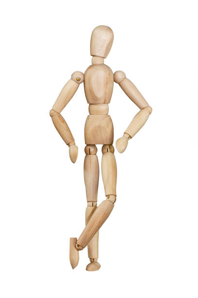 Wooden mannequin isolated on white background Wooden mannequin trying to represent human movements in moving actions isolated on a white background. Anatomical model with hands on hips and crossed legs. ventriloquist's dummy stock pictures, royalty-free photos & images