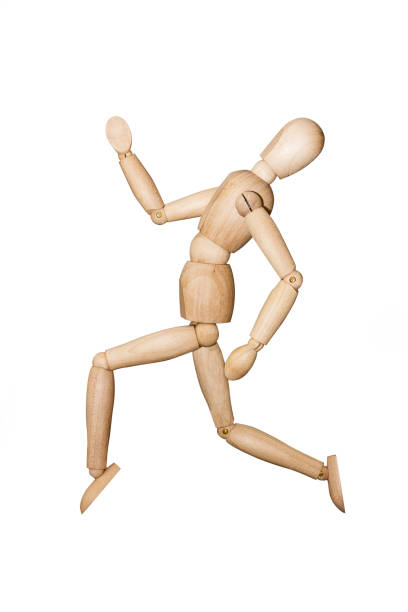 Wooden mannequin isolated on white background Wooden mannequin trying to represent human movements in moving actions isolated on a white background. Anatomical model runs in finishing line with torso in the back. ventriloquist's dummy stock pictures, royalty-free photos & images
