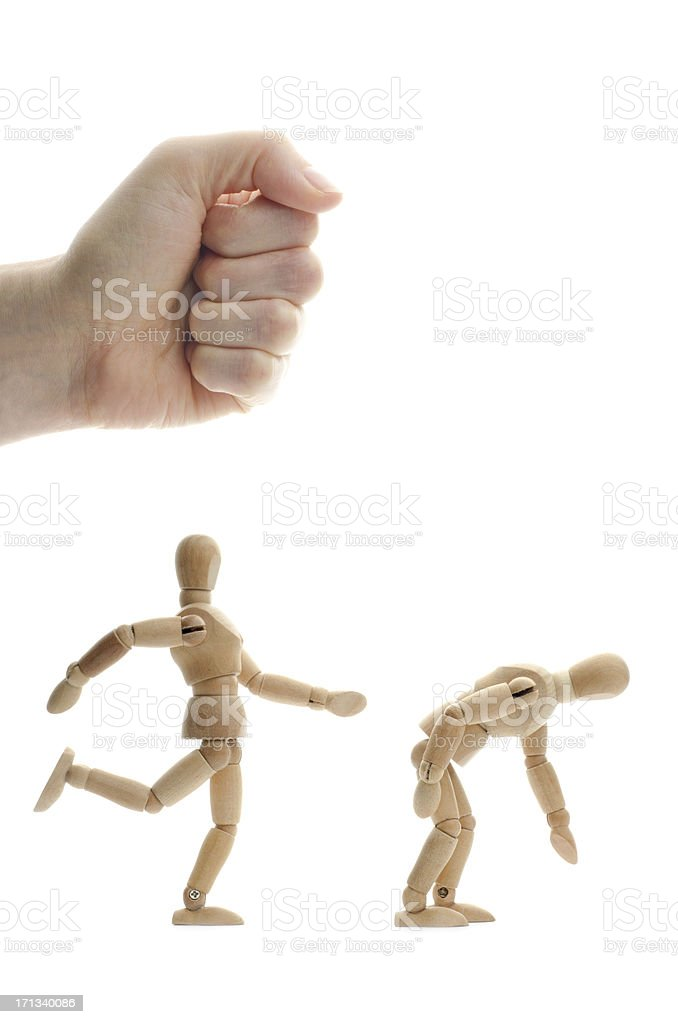 wooden mannequin kicking another in the butt stock photo