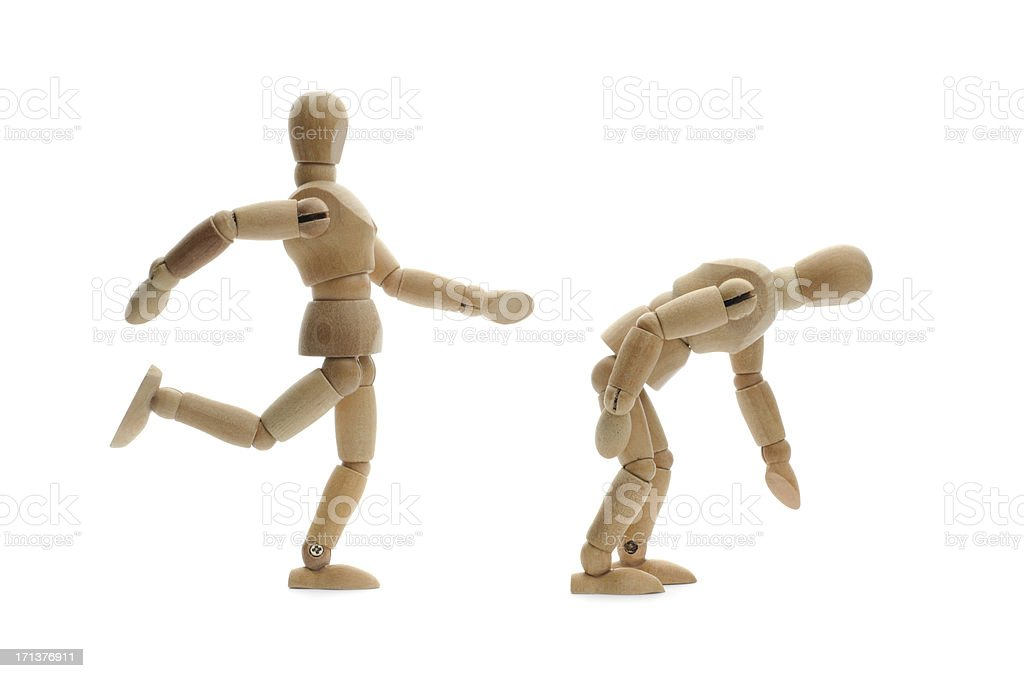 wooden mannequin kicking another in the butt royalty-free stock photo
