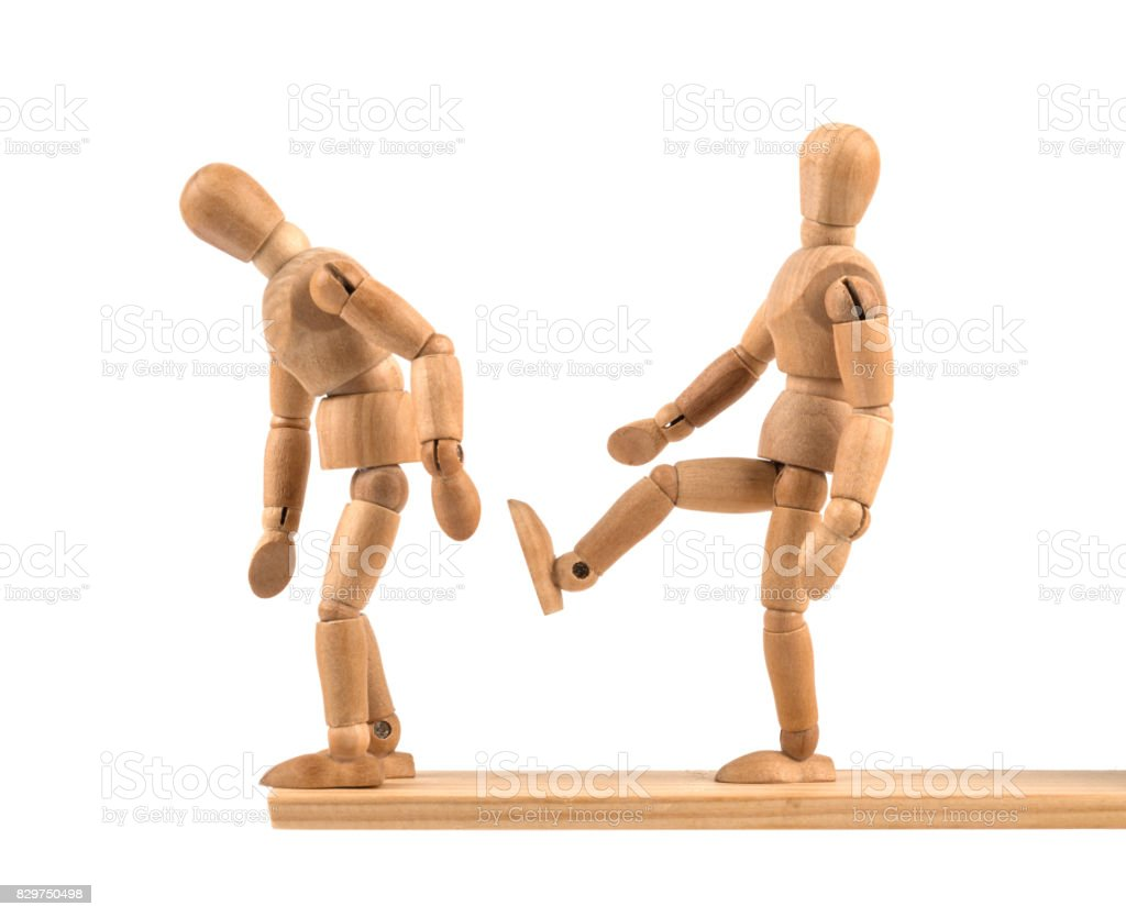 Wooden mannequin kicking the rival in the deep stock photo
