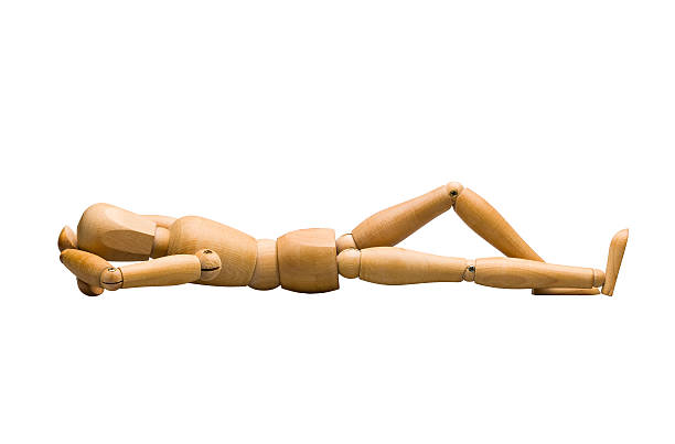 Wooden mannequin lying down Wooden mannequin lying down, isolated on white. ventriloquist's dummy stock pictures, royalty-free photos & images