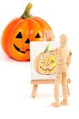 Wooden mannequin painting Halloween pumpkin.