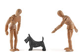 Wooden mannequin pointing on black dog. Is this yours? stray dog?