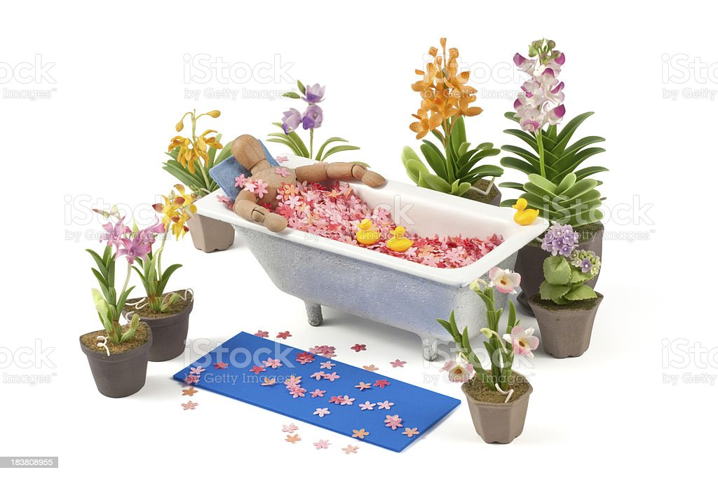 wooden mannequin relaxing in bathtub with flowerbath royalty-free stock photo
