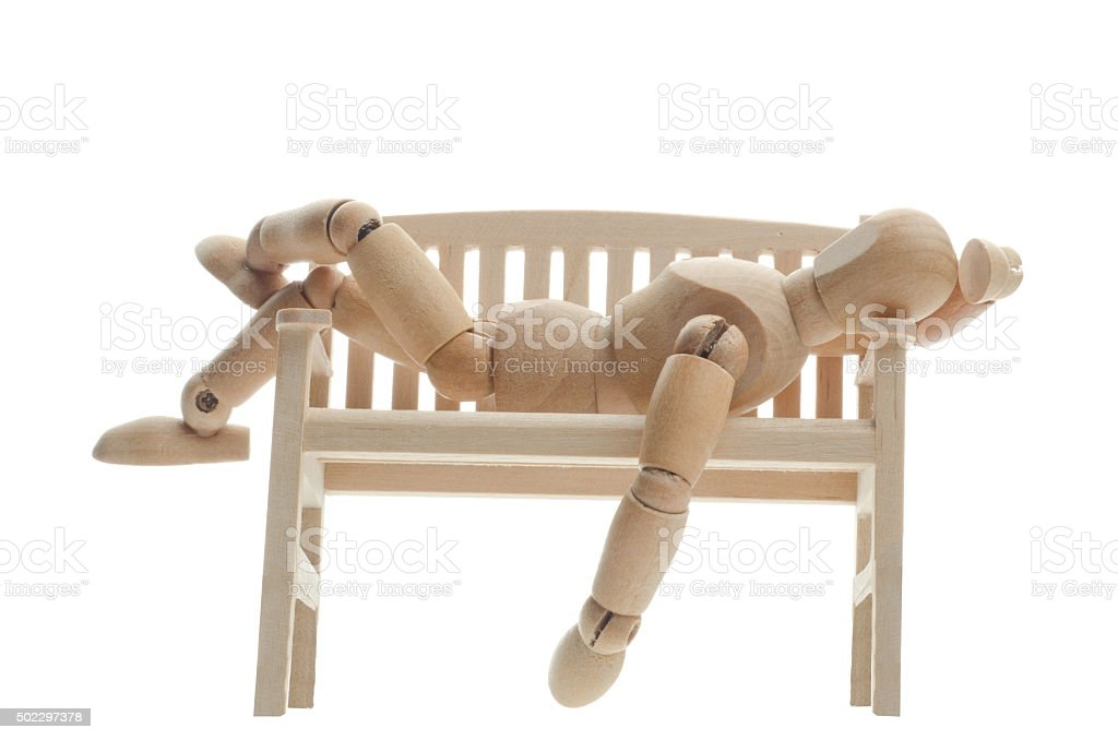 wooden mannequin relaxing on a bench and looking in sky stock photo