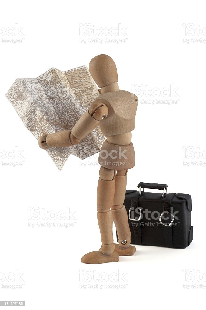 wooden mannequin searching the way in map stock photo
