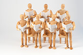 Wooden mannequin singing together in the choir with sheet music