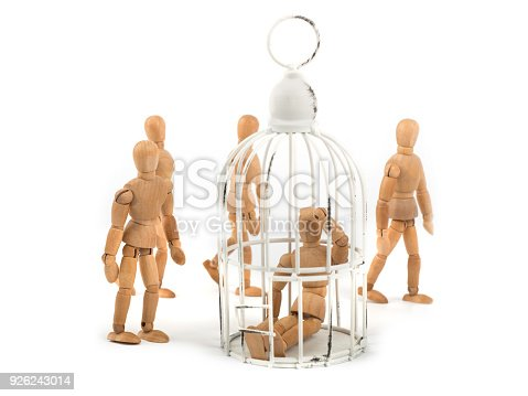 istock Wooden mannequin sits in cage in crowd - depression? helpless? ignorance? 926243014