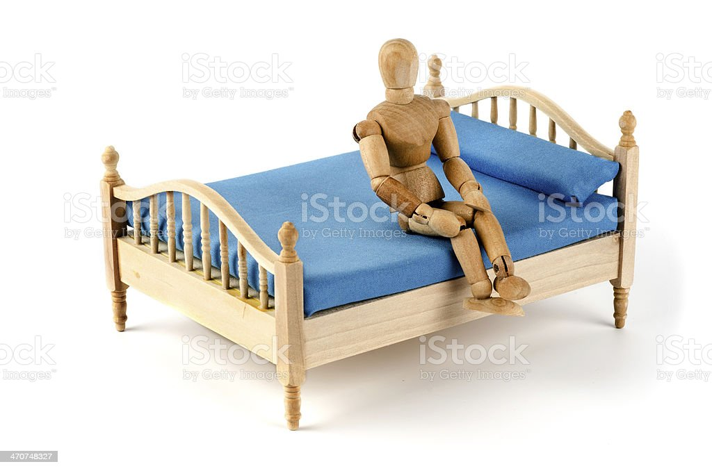 wooden mannequin sitting in bed stock photo