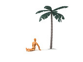 Wooden mannequin sitting on lonely island under a palm