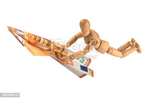 wooden mannequin surfing on Euro money note